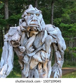Quadra Island, BC / Canada - August 19, 2019: Colse up of driftwood sculpture of Sasquatch strolls through the clearing in the forest on Rebecca Spit