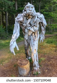 Quadra Island, BC / Canada - August 19, 2019: Driftwood sculpture of Sasquatch strolls through the clearing in the forest on Rebecca Spit