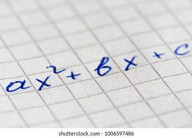 The quadratic equation is written in blue pen on squared paper