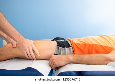Quadriceps massage to an athlete by a physiotherapist.