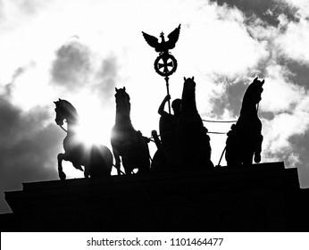 quadriga with the symbol of the Roman Empire of the Brandenburg Gate in Berlin against the light