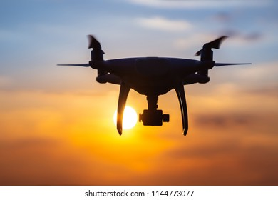 The quadrocopter in the air on the sunset background