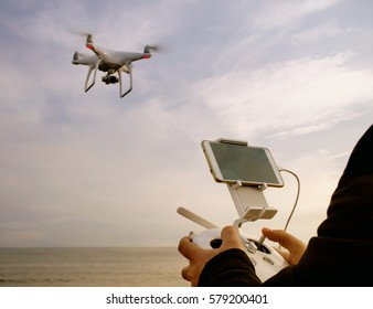 quadrocopter drone with remote control unit at man hands