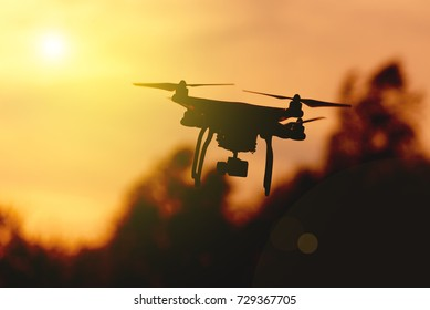 Quadrocopter flies in the air at sunset. Launching a quadrocopter in the park