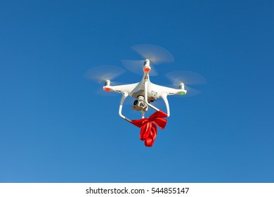 Quadrocopter with red ribbon flying high in the sky