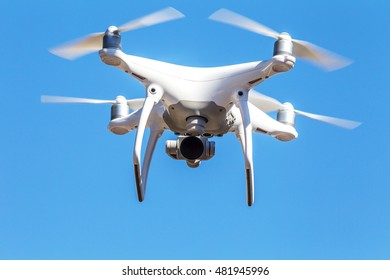 Quadrocopter unmanned camera hovers in bright blue sky above city on background of urban buildings Modern technology photo and video shooting bird's-eye view. Professional Carbon Quadrocopter with GPS