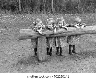 Quadruplet girls leaning on wood fence
