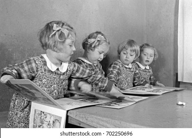 Quadruplet girls reading story books together