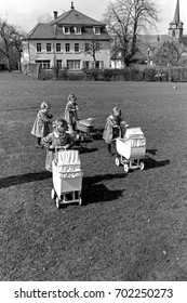 Quadruplet little girls pushing toy carriages across lawn