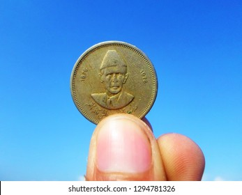 Quaid-e-Azam`s 100th anniversary 50 Paisa Coin-A Person is holding Muhammad Ali Jinnah portrait Historic golden coin, sharp blue sky is in background. It was issued on 100th anniversary of Jinnah