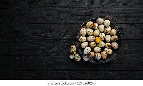 Quail eggs in a black plate. On the old background. Top view. Free copy space.