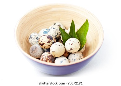 Quail eggs in bowl with leaves. With clipping path.