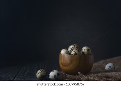 Quail eggs in a bowl on a black background in moody light