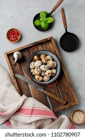 Quail eggs in metal plate on gray old background. Rustic style. Top view.