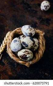 Quail eggs in nest over black metal background.