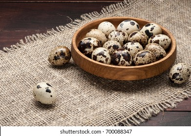 quail eggs in wooden plate over dark old wooden background