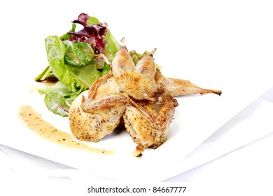 Quail with green and purple salad on white plate
