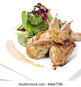 Quail with green salad on white plate