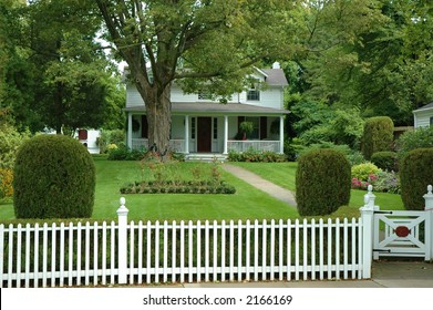 Quaint beautiful house with green yard and white picket fence
