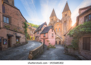 The quaint and charming town centre of the  medieval French village Conques, Aveyron and Abbey Church of Sainte-Foy at sunset or sunrise in Occitanie, France.