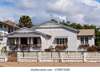 A quaint cottage filled with flower boxes and a white picket fence