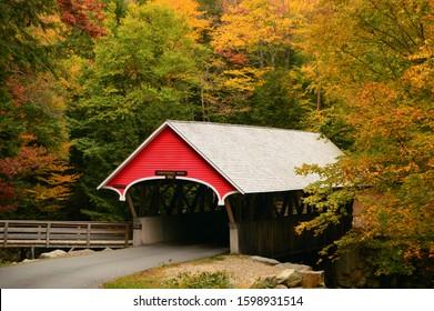 A quaint covered bridge is surrounded by brilliant autumn foliage