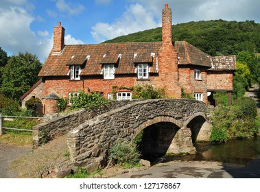 Quaint English Village Cottage beside a stream and ancient stone Packhorse Bridge and Ford