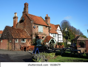 Quaint English Village Inn with seating area and garden to the front against a clear Blue Winter sky