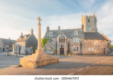 Quaint, historic medieval village of Corfe, Dorset, England with golden hour sunset or sunrise summer light.