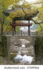 A quaint little bridge near a Korean temple hidden in the Autumn (Fall) foliage.