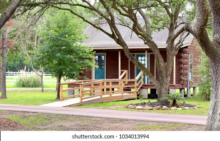 A quaint log cabin surrounded by trees and a well maintained garden with turquoise doors and an overpass bridge. Perfect for a nice retreat.