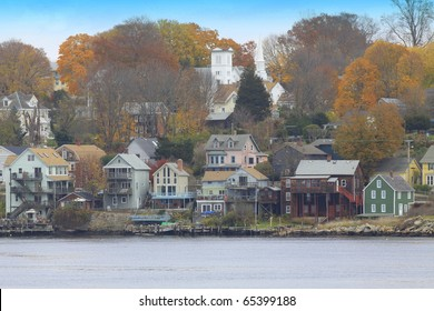 a quaint new england town's houses  on the water where the boats carry passengers