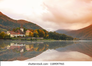 Quaint picturesque small fairytale town on the shore of the Danube River in Austria in the Fall with misty mountains in the background