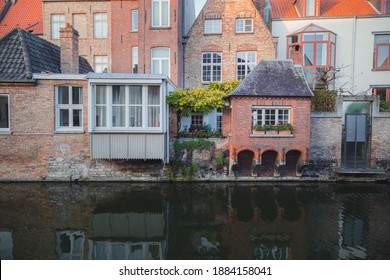 Quaint red brick homes alongside a quiet canal in old town Bruges, Belgium.