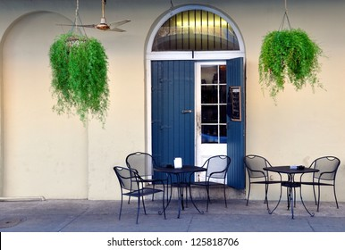 A Quaint Sidewalk Cafe In The New Orleans French Quarter With Hanging Ferns