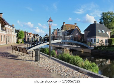 The quaint town of Kollum in Friesland in the Netherlands on a sunny summer's evening. View of the Trekvaart waterway, waterfront houses and the pedestrian bridge.