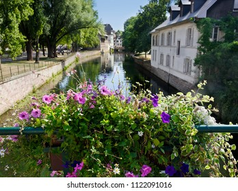 Quaint village of Strasbourge with water canals and decorative floral arrangements.