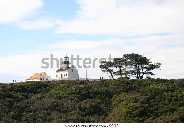 quaint white lighthouse with neighboring trees