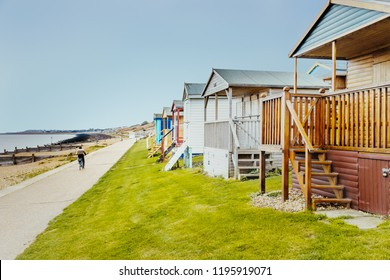 Quaint wooden beach huts in a row along a grass verge in front of the promenade that a man is cycling along, by the beach and sea in Tankerton, Whitstable, Kent, UK