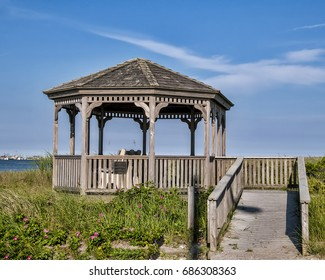 A quaint wooden gazebo along the shore on a bright sunny day in summer