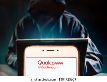 Qualcomm logo is seen on an Android mobile device with a figure of hacker in the background.