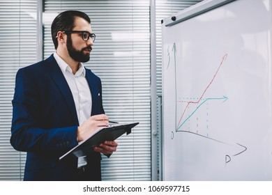 Qualified business coach in formal wear discussing graphic schemes drawn on flipchart during productive workshop.Pensive trader analyzing schedule of report standing near board in office interior