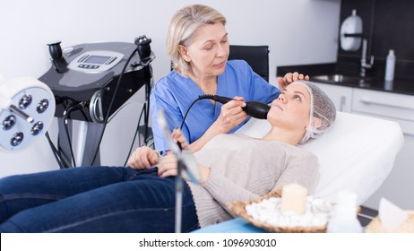 Qualified female beautician with client during hardware facial procedure in modern aesthetic clinic