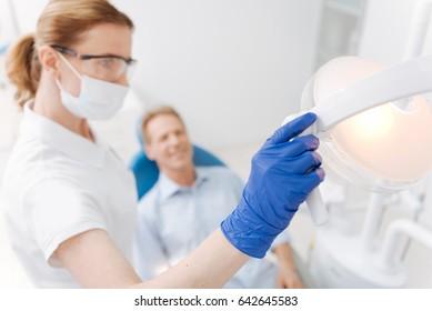 Qualified mindful dentist adjusting the lights