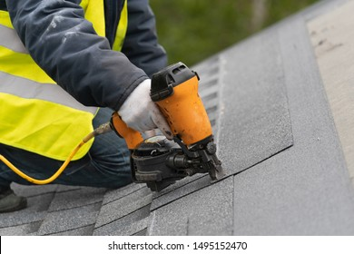 Qualified roofer worker in protective uniform using air or pneumatic nail gun and installing asphalt or bitumen shingle on top of the new roof under construction residential building