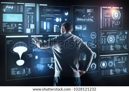 Qualified specialist. Calm clever experienced programmer standing with his hand resting on his hip and thoughtfully looking at the information on a transparent screen