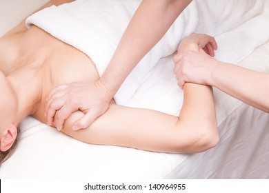 A qualified therapist doing a pressure point massage to relax  a woman's shoulder
