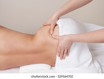 Qualified therapist  doing pressure point massage on a woman's hip