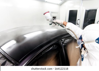 qualified worker spraying black paint on a car in special painting booth