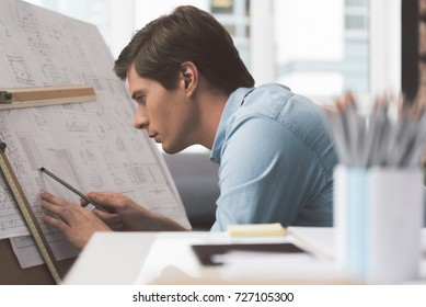 Qualified youthful architect is working on building plan